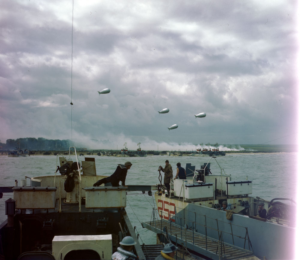 A colour photograph showing a landing craft approaching the beach, with smoke coming from a village and barrage balloons overhead.