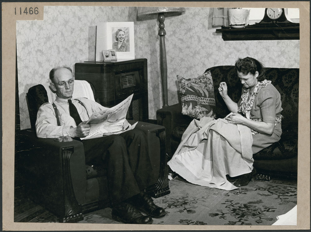 A black-and-white photograph of a man sitting in an armchair reading a newspaper. A woman sits on a couch and sews.