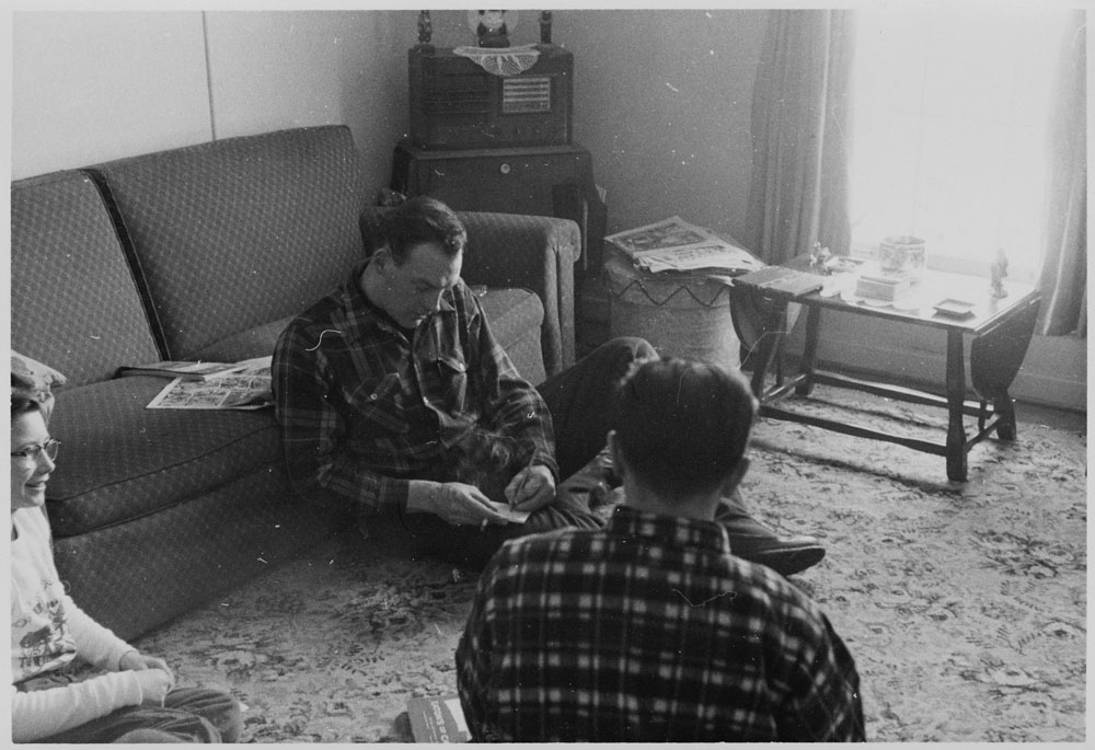 A black-and-white photograph of man sitting on an area rug with friends. He is leaning against a couch, smoking a cigarette, and writing in a notepad.