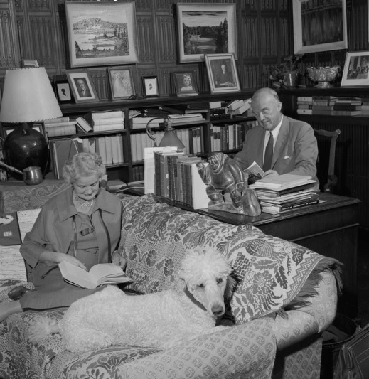 A black-and-white photograph of a woman sitting on a couch reading a book beside her poodle. A man sitting at a desk next to the couch reads a magazine.