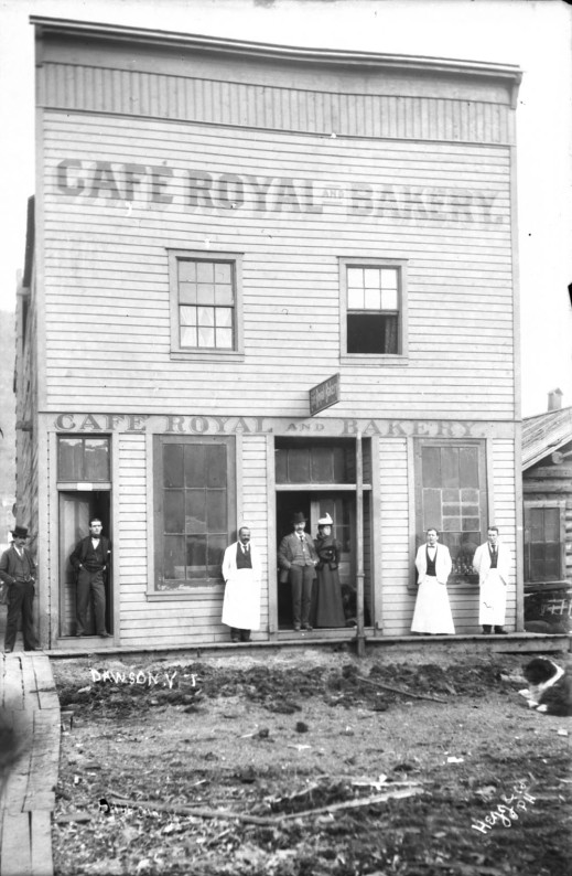 "A wooden building with ""Café Royal and Bakery"" painted on it. Three waiters and four customers stand on the boardwalk in front of the building."