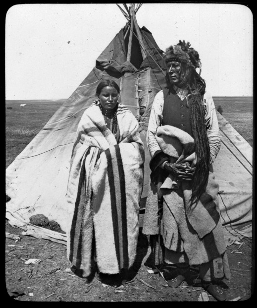 A black-and-white photograph of Poundmaker standing in front of a tipi wearing a fur hat, a shirt and vest, a blanket around his waist, and moccasins. Standing next to him is his wife, wearing a blanket around her shoulders over a dress.