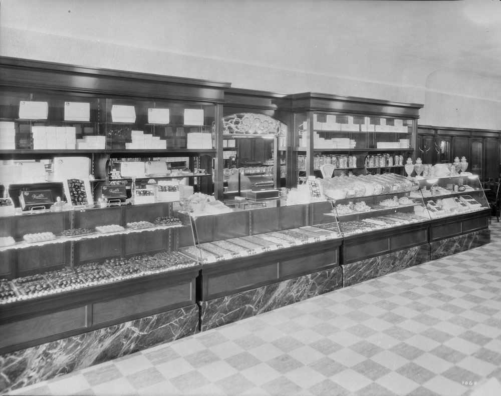 Four glass cases packed with baked goods form a long counter. Tall wooden shelves with a mirror in the middle are lined with boxes. The floor has a checkerboard pattern.