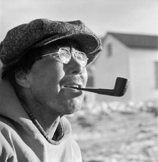 Close up portrait of a man smoking a pipe, and wearing a flat cap and round glasses.