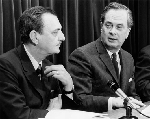 A black-and-white photograph of two men with a microphone between them.