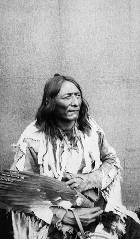 A black-and-white photograph of Isapo-Muxika (Crowfoot), seated holding an eagle feather fan and wearing a hide shirt adorned with fur and beads or quills.