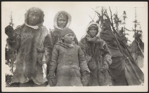 A black-and-white photograph of an Innu man and three members of his family. The men and young boy are dressed in fur jackets and mittens. A tent and trees are in the background.