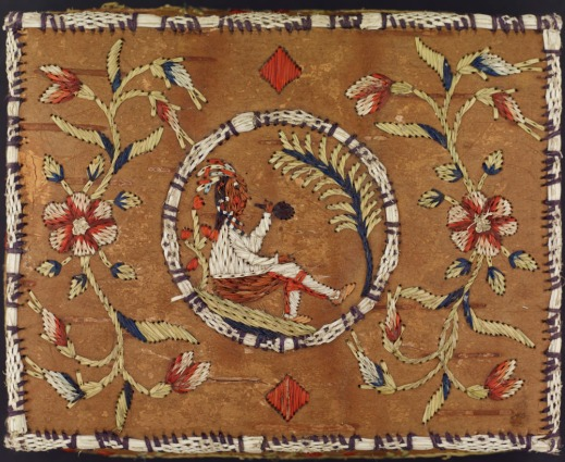 A birch bark basket embroidered in the centre with a First Nations figure smoking a pipe, and white, red, and blue flowers on each side.