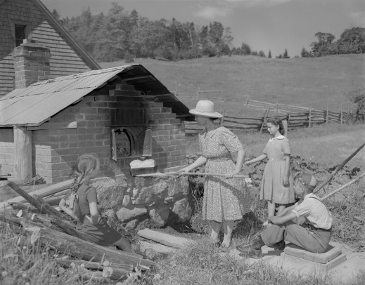 Three children watch while their mother pull bread from an outdoor brick oven. A house and a field can be seen in the background.