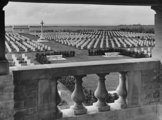 A black-and-white photograph showing many rows of Imperial War Graves Commission headstones, and a large Cross of Sacrifice.