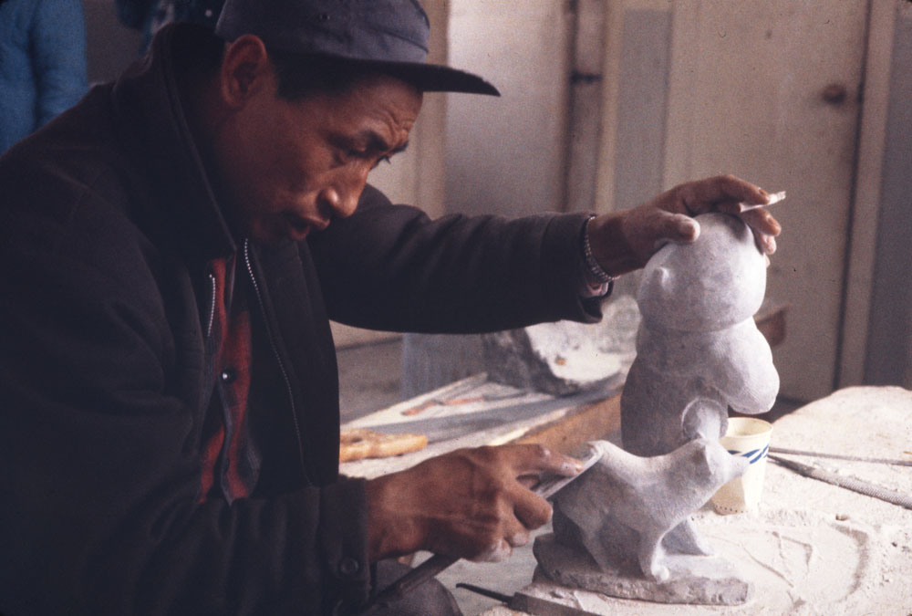 A colour photograph of an Inuk man wearing a dark jacket and cap as he carves white statues.