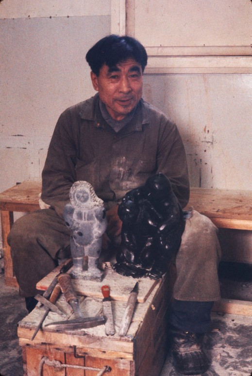A colour photograph of an Inuk man sitting behind a stone sculpture with his tools in front of it.
