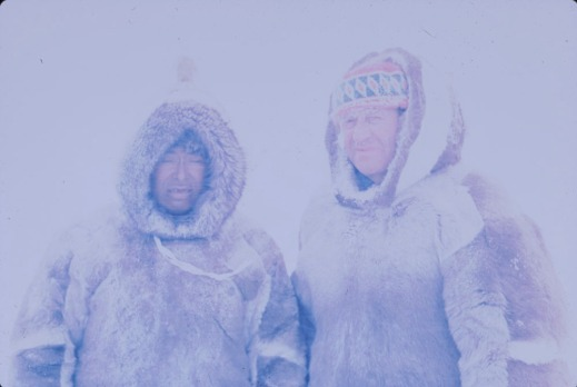Colour photograph of an Inuk man, Kove, and Charles Gimpel dressed in brown-and-white fur parkas. The photo is very hazy because of a snowstorm.