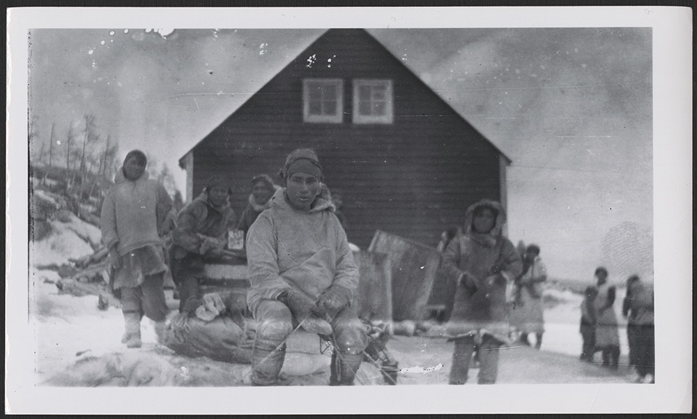 A black-and-white photograph of an Innu man staring at the camera, wearing traditional clothing and sitting on a pile of supplies. In the background, many other people are standing in front of a dark-coloured house with two small windows.