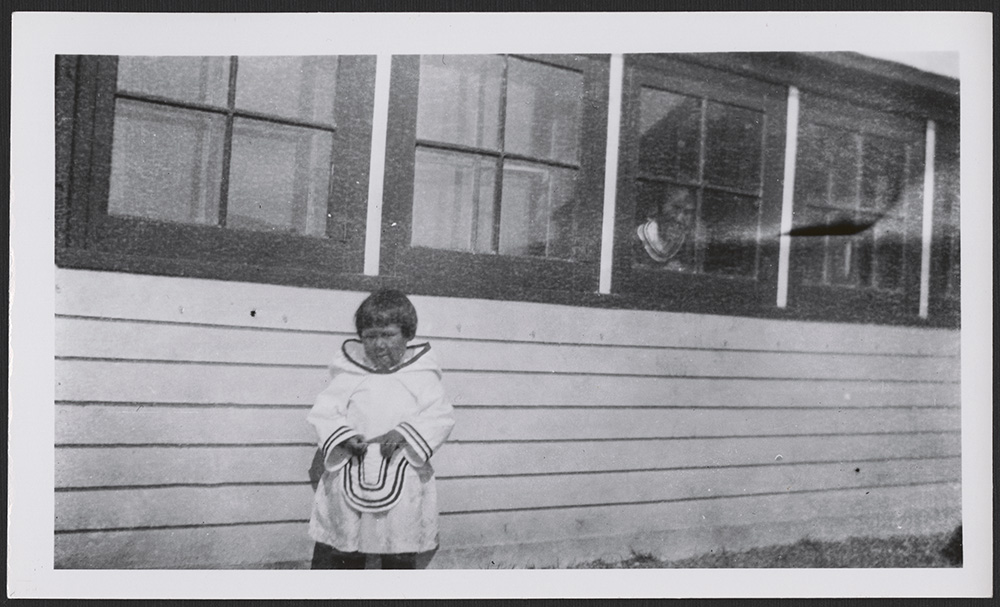 A black-and-white photograph of an Inuk girl facing the camera. The young girl is wearing a white amauti (a girl's or woman's coat with a large hood) and stands in front of a building as a woman peeks out from a window behind her.