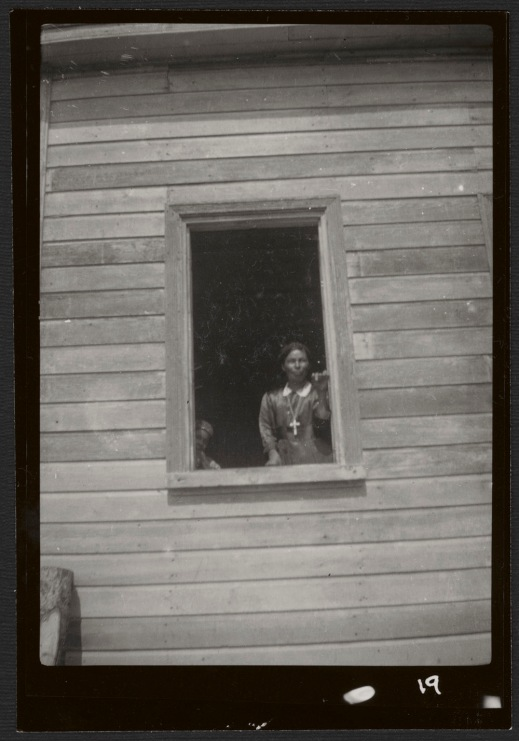 A black-and-white photograph of a woman standing in a window of a wooden building, wearing a dress with a white collar and a necklace with a large cross. In the left-hand corner of the window frame, a child is peeking out, looking toward the camera.