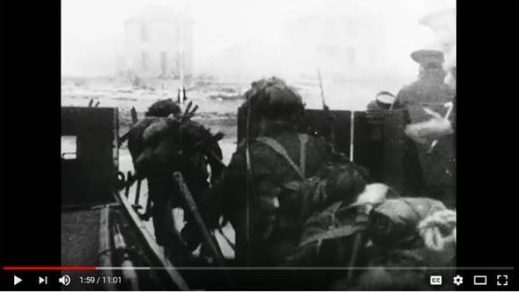 A black-and-white image taken from moving film, showing soldiers exiting a landing craft.