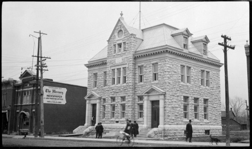 "A black-and-white photograph of a large stone building. In front of the building, there are men walking on the sidewalk. The sign on the building next door reads ""The Mercury Newspaper."""