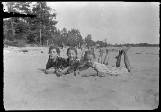 A black-and-white photograph of three girls lying side by side on the sand on their stomachs.