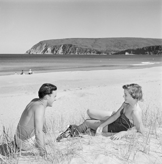 A black-and-white photograph of a man and a woman sitting on the sand, facing each other and smiling.
