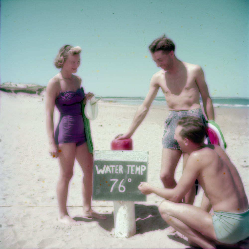 A colour photograph of a woman and two men. One of the men crouches and marks the water temperature in chalk on a sign as 76 degrees Fahrenheit.