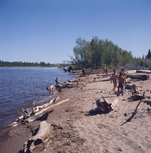 A colour photograph of a group of boys playing on the beach at a lake.
