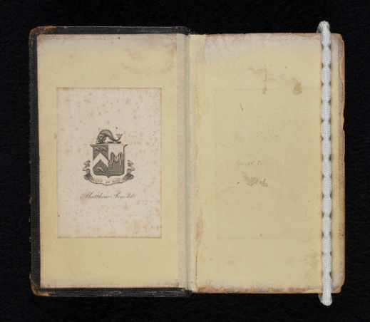 A book open to the inside front cover. Attached to the left-hand page is the bookplate of Matthew Arnold. The right-hand page is blank and held down by a weight.