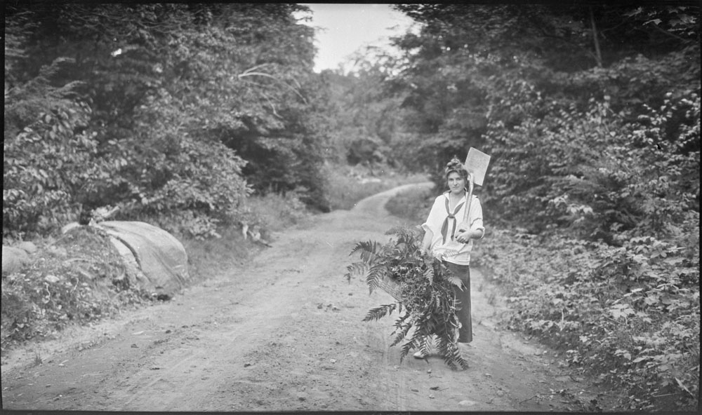 Black-and-white photograph of a woman standing on a dirt road holding a basket full of fern leaves and a shovel on her left shoulder.