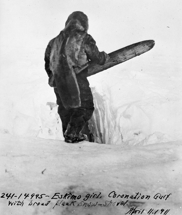Black-and-white photograph of a woman using a traditional wooden broad plank snow shovel to build an igloo.