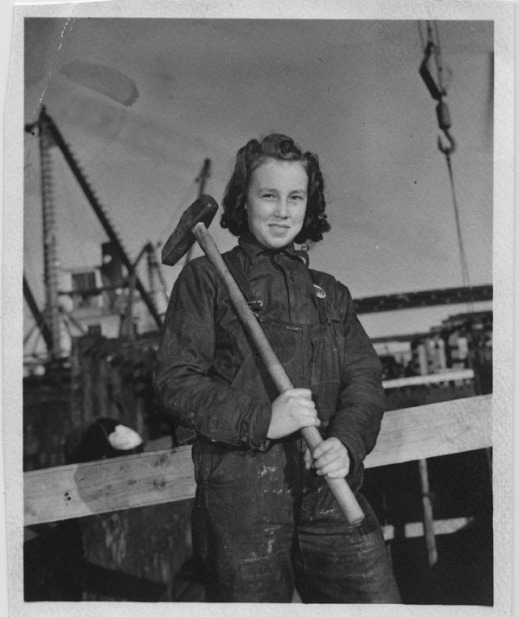 Black-and-white photograph of a girl holding a sledgehammer that rests on her right shoulder.