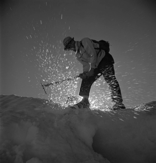 Black-and-white photograph of a man leaning forward and swinging an ice axe to break ice.