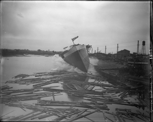 A black-and-white photo of the launching of a ship into the water, surrounded by logs and other debris.