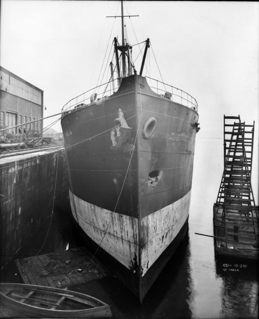 A black-and-white photo of the front of a large ship. There is a dent on the side of the hull that is furthest from the dock.