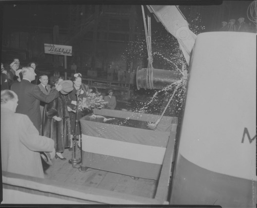 A black-and-white photo of men and women watching a champagne bottle being broken against the hull of a large ship. A man is holding his hat over the face of a woman wearing a fur coat.