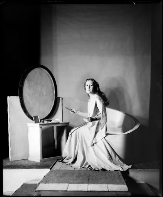 Black-and-white photograph of a woman with long dark hair in a flowing white dress, seated in front of an oval mirror and looking toward the camera.