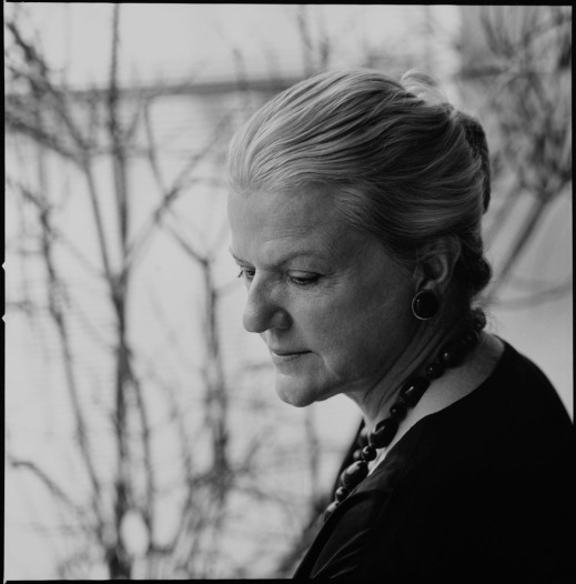 Black-and-white photograph of a woman in profile with grey hair and a dark necklace.