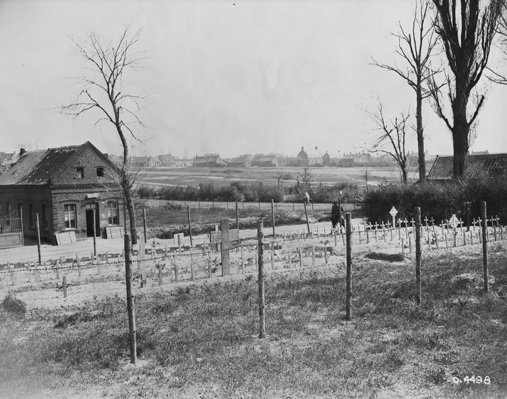 A black and white photograph of a cemetery behind a fence and small leafless trees near Cambrai, France. There is a house and a farm in the background.