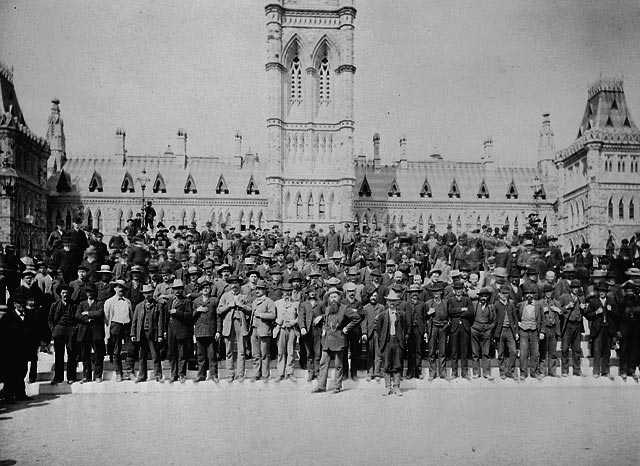 A black-and-white photograph of a large group of men standing in front of the Parliament buildings.