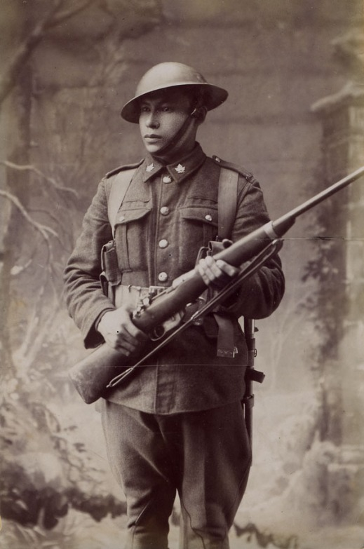 A black-and-white studio portrait of a First World War soldier in uniform and holding a rifle.
