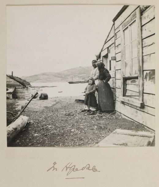 A black and white photograph of two Inuit women and an Inuit child standing beside a wooden house.