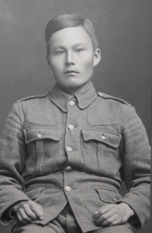 A black and white photograph of a young Inuk man in a military uniform staring towards the camera.