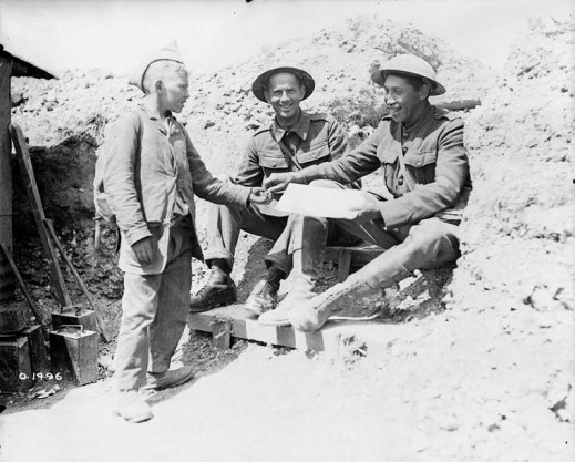 A black-and-white photograph of two men in First World War military uniforms smiling and buying a newspaper from a young boy. The man on the right is accepting a newspaper from the boy and giving him money in exchange.