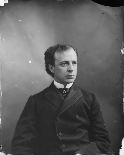 Black-and-white photo of a seated man in a suit.