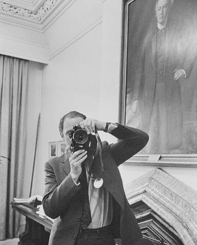 Black-and-white photo of a man taking a photograph of a photographer who is photographing him.