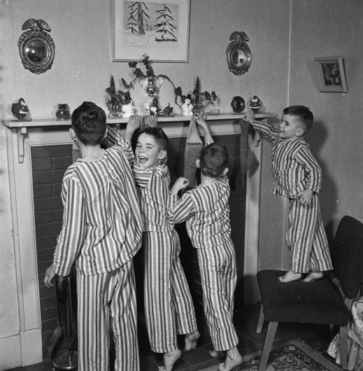 Photograph of four boys in matching striped pyjamas hanging Christmas stockings on a fireplace mantle.