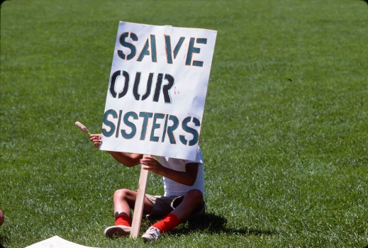 "Colour photograph of a person sitting on green grass behind a sign that reads ""Save our sisters."""