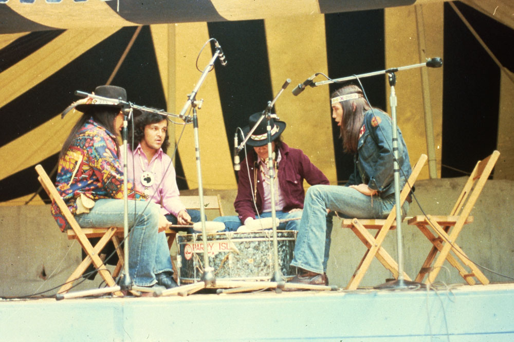 Colour photograph of four men sitting on wooden chairs surrounded by microphones and facing each other, singing and drumming.