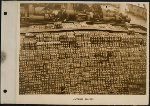 Photograph of workers with hundreds of crates of oranges on a ship deck.