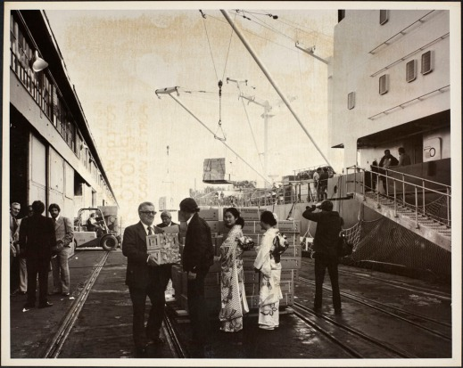 Photograph showing port officials holding boxes of mandarin oranges, two Japanese women in traditional dress standing by a pallet of orange boxes, and other people and equipment on a pier adjacent to a ship.