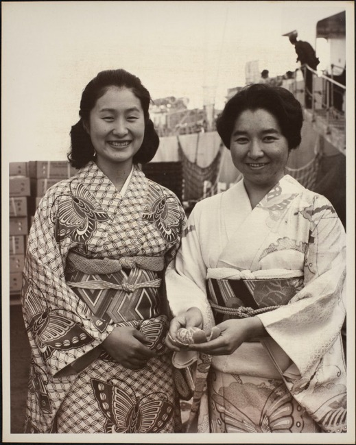 Photograph of two Japanese women wearing traditional dress, one of whom is holding a peeled mandarin orange. Crates of oranges and a ship are visible in the background.